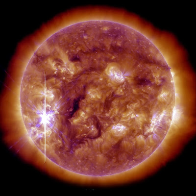 This handout picture released by the NASA and coming from the Solar Dynamics Observatory (SDO) on November 5, 2013 shows the Sun brightened when an X-class solar flare—the largest so far this year—burst from a large, active sunspot. The flare followed a series of more than a two dozen flares that have occurred since October 21, though the November 5 flare originated in a different active region. The event was classified an X3.3 flare, falling into the category of most intense explosions. This view of the flare comes from NASA's Solar Dynamics Observatory (SDO), and it shows the Sun in extreme ultraviolet light (blending 193 and 131 angstrom observations). The long streak of light is likely due to solar protons saturating the imager. The unusual color is due to the blending of false colors that are assigned to each wavelength by solar physicists to distinguish the different bands. The image is from 5:12 p.m. Eastern Standard Time (22:12 UTC), the peak of the short flare.