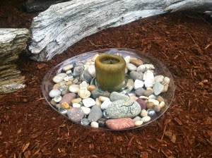 Unlit candle sitting in a clear, shallow bowl filled with rocks. The bowl rests upon bark groundcover and a small log is in the background.
