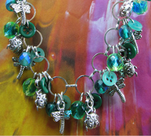 Charm necklace has clusters of beads and buttons in green with silver dragonfly and ladybug charms