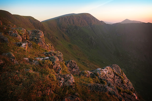 A warm glow lighting up striding edge and the Helvellyn range, sunrise, wild camp