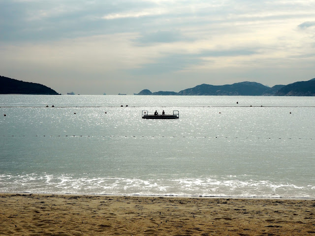 Silhouettes of girls on a raft in the ocean off Repulse Bay Beach, Hong Kong