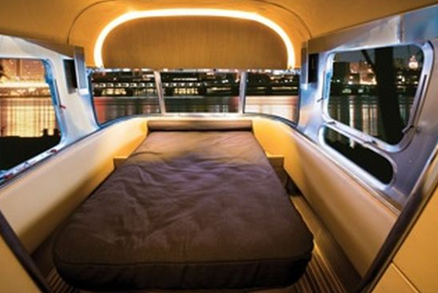 bedroom of airstreams land yacht luxury trailer and vanity caravan with night skyline outside window