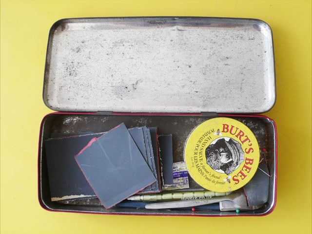 A metal tin which contains sandpaper, 'hurts bees' balm, pencil, a spoon and a few other random items.