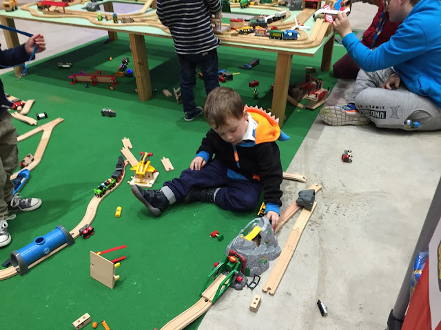 Child building a train track made for BRIO