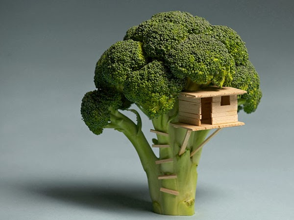 Piece of broccoli that has a miniature tree house in it