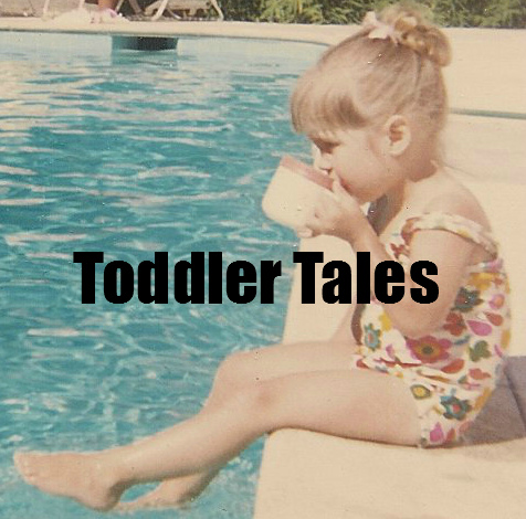 Toddler sitting by the pool sipping a mug