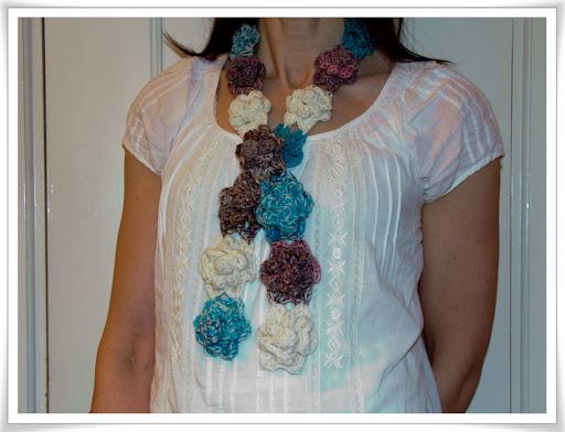 Virkade blommor av melerat garn på rad, en smal sjal