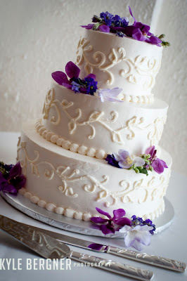 White wedding cake with purple flowers and swirls