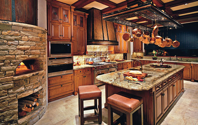 Lots of rich warm woods used here, love the pizza oven and storage for wood  underneath, you could have some fun pizza parties in this kitchen!