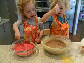 Adding pink colouring and cocoa to mix for Rainbow Cake.