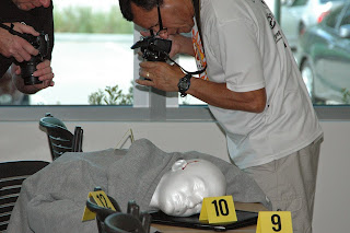 Teachers photograph a mock crime scene.