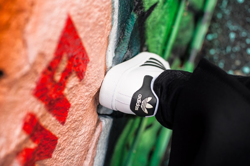 Adidas Superstar black and white sneakers from the back against a grafitti coloured wall