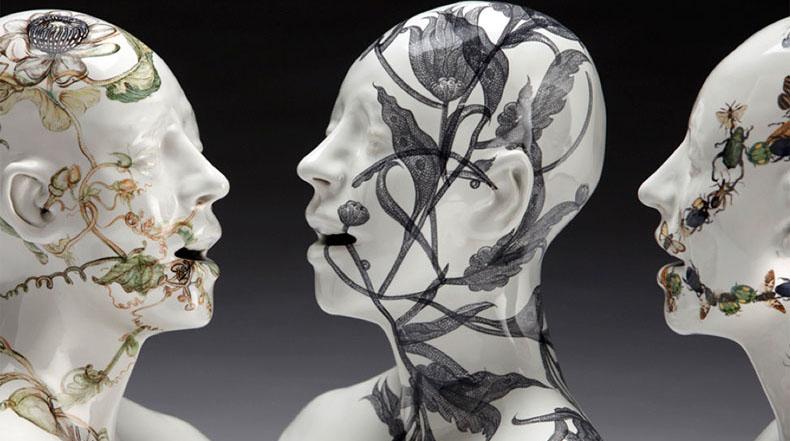 Rostros de cerámica invadido por la vegetación por Jess Riva Cooper