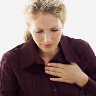 Woman with heart burn clutching her chest