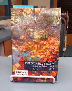 Oregon Blue Book almanac and fact book for 2015-2016, standing upright in a wire stand on a library counter