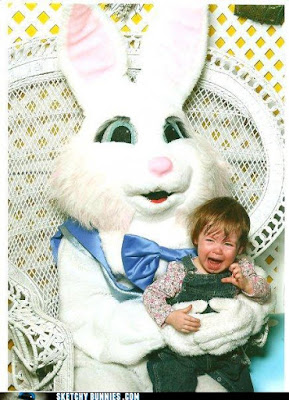 A crying child sits with a bunny-costumed adult