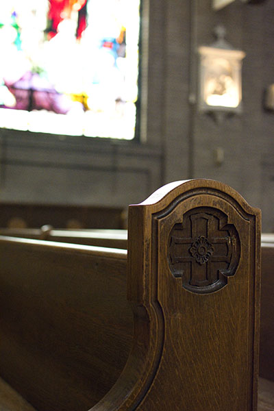 Cross and rose carved into the worn wooden pew of St. Lawrence Basilica with a strongly lit stained glass window in the background