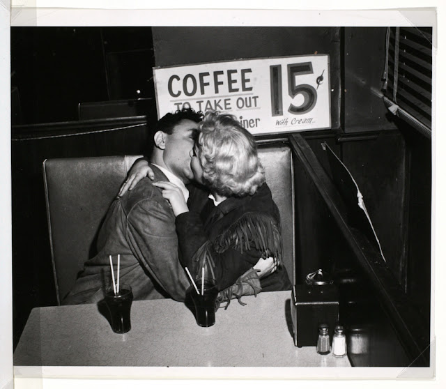 Young lovers kissing in diner, 1950's
