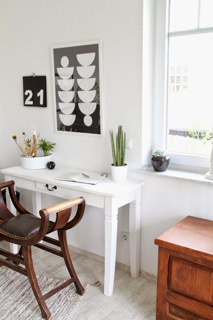 Schräge Ansicht auf den weißen Schreibtisch mit Blumenampel als Pinselhalter und Pflanzen