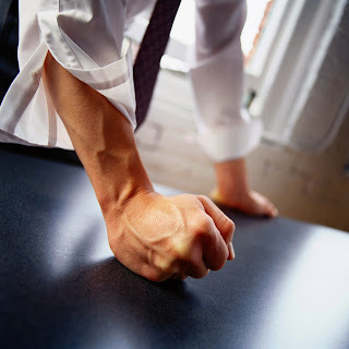 Man's clenched fist banging on a table.