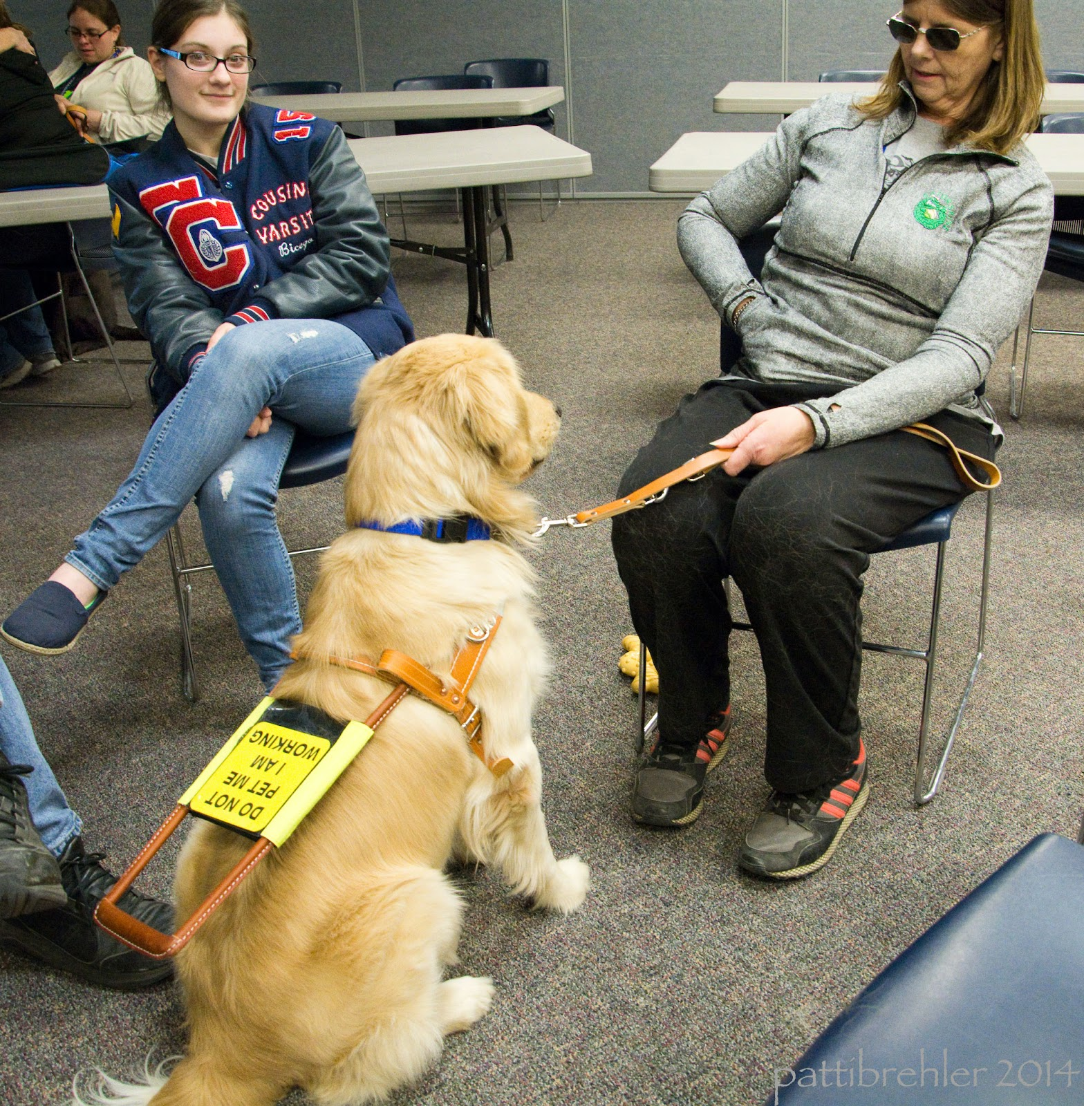 In this photo,  only the teenager (on the left) and the woman with sunglasses are in view. The teen has her legs crossed, sitting in the chair. The woman is reaching into her shirt pocket with her right hand while holding the dog's leash with her left. The golden is sitting in front of her facing her, almost at attention. The dog has a guide harness on.