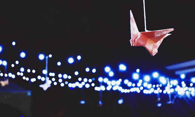 Fairy lights strung up and lit against the night sky with a paper crane suspended in the foreground of the photograph.