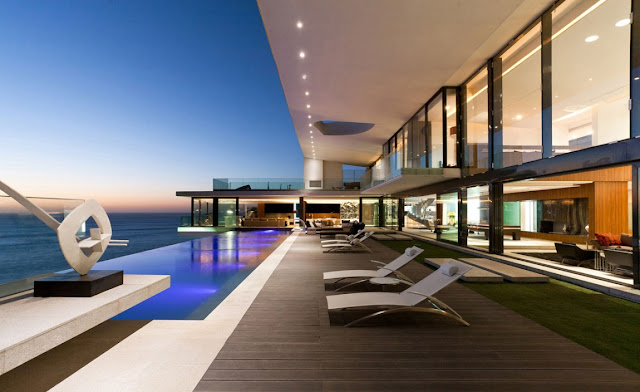 Picture of the house and the ocean as seen from the terrace by the pool at sunset