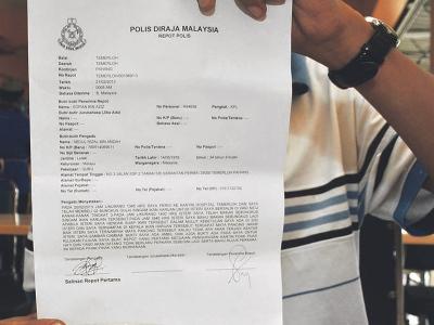 Abdul Rizal memegang laporan polis yang dibuatnya berhubung penemuan mata kail dalam lauk singgang ikan haruan dibeli di kafe HosHAS.