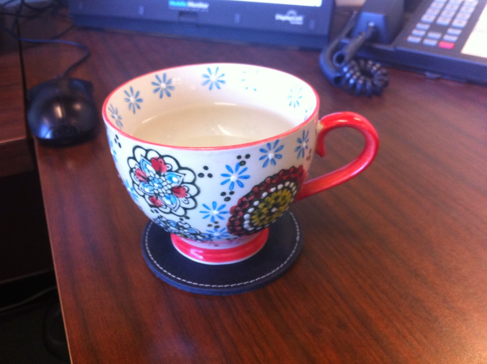 Tea cup with orange and blue flower, filled with warm water.