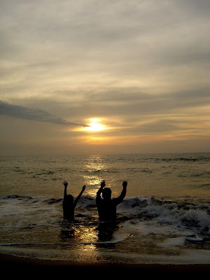 kids raising hands at sunset