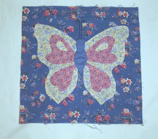 Butterfly applique with needle-turned edge on blue print fabric