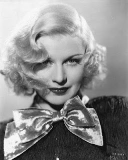 Ginger Rogers with short wavy blonde hair wearing a dark button up shirt and a huge silver bow at the collar.