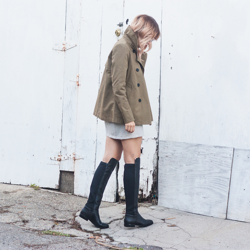 easy stylish outfits for every kind of woman, An Everlane trench coat paired with a tee shirt dress and tall over the knee black boots from Cole Haan
