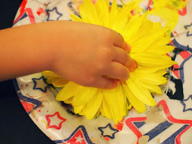 place flower head into paint to print with flowers