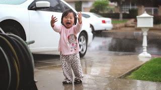 Une petite fille s'émerveille devant la pluie pour la première fois