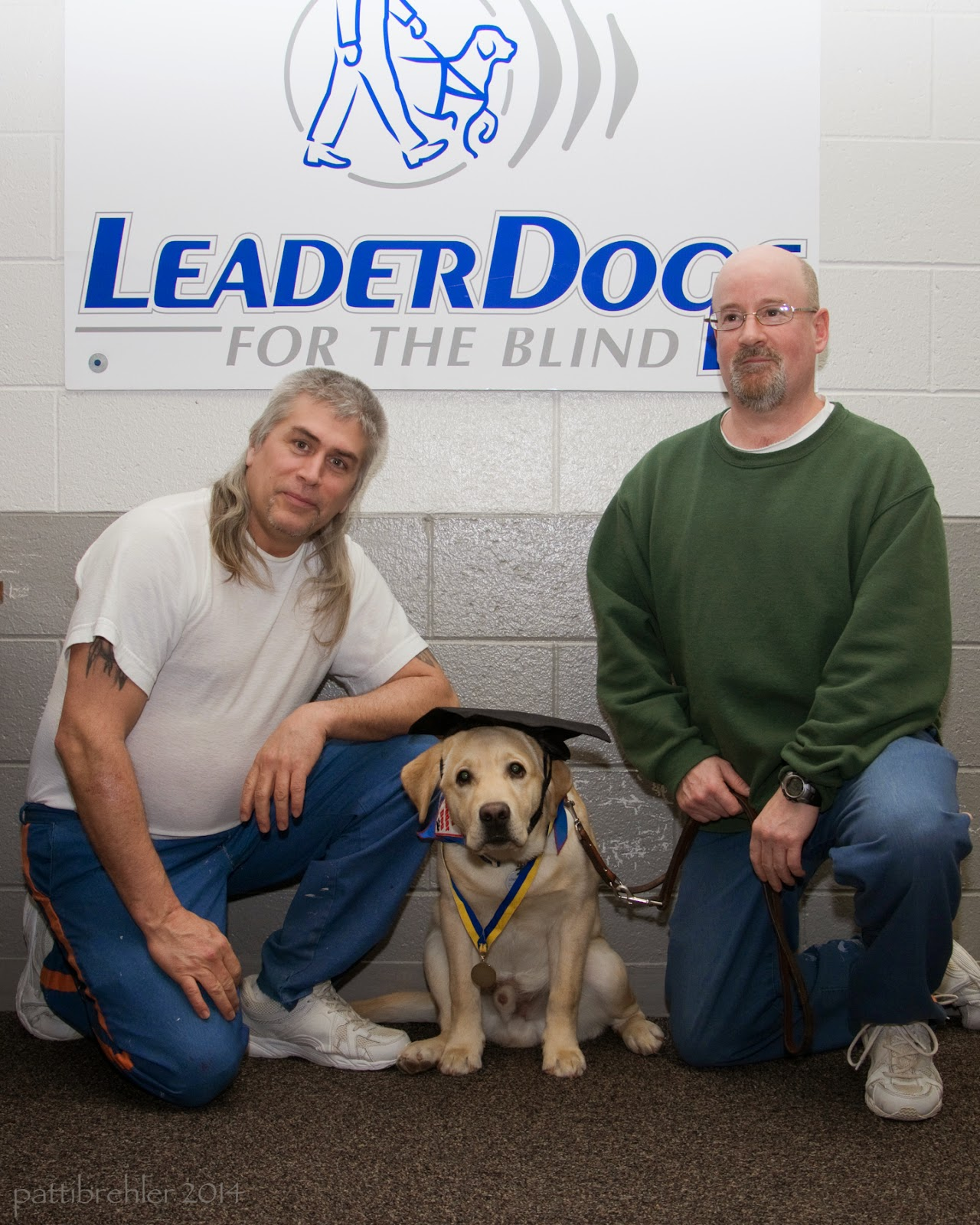 Two men are kneeling on one knee in front of a Leader Dogs for the Blind banner, looking at the camera. The men are wearing blue prison pants, the man on the left is wearing a white t-shirt and the man on the right is wearing a green sweatshirt. Between them is a young yellow lab that is sitting looking at the camera with a graduation cap on his head.