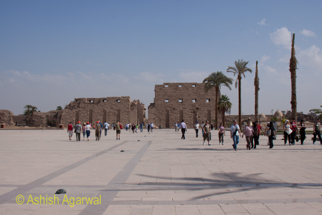 View of the front pylons of the Karnak temple at Luxor, and tourists returning from it