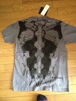 """グレイ・フォックスの背面のTシャツ.全面には""""Neither Enemy Nor Fiend""""と描いてあります."""