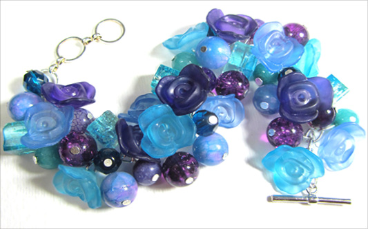 Chunky bracelet has shiny blue and purple flower buttons with fire polished czech beads and crackle beads