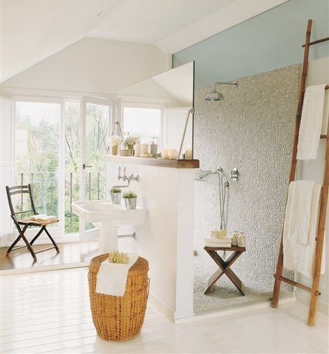 Bathroom with white painted wood floors, double french doors leading to a small patio, a shower open on both sides with one wall doubling as a backsplash for the pedestal sink and pebble mosaic on the walls and floor