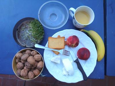 Blauer Tisch, ziegelrote Fliesen und das beschriebene Essen darauf im Abendlicht.