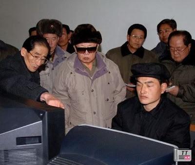 Cố lãnh đạo Kim Jong-il (đeo kính râm) làm việc với các chuyên gia máy tính hồi năm 2009 - Ảnh: Reuters