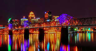 colorful photo of the big four bridge lit up at night with blue, green ornge lights reflecting into the river and the large buildings in the background
