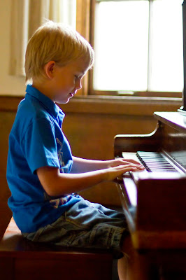 Maxton playing the piano at the piano recital