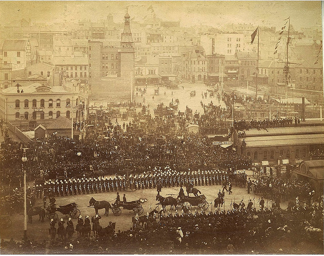 """Arrival of Governor Sir Robert Duff, Circular Quay, Sydney, June 1893 / photographer unknown. Note: the sailing ship called the """"Convict Hulk Success"""", a commercial exhibit, upper right, and the bald-faced building with two towers which is a fire station, upper left."""