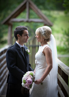 Bride and groom looking at each other. Bride wears lace gown and is holding a bouquet. Her hair is styled in a bouffant sixties style