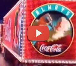 """Propaganda antiga da Coca-Cola """"O Natal Vem Vindo"""" com caminhões chegando na cidade."""
