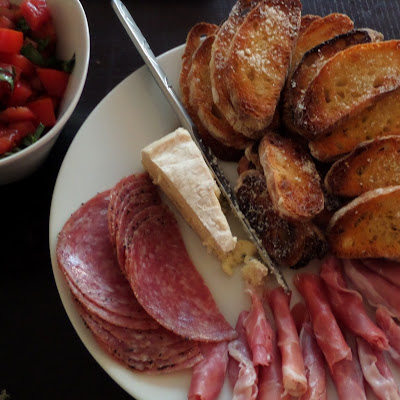 Diced tomatoes and basil to top thinly sliced ciabatta toast with a meat and cheese platter.  Great as an appetizer and filling enough for a meal.