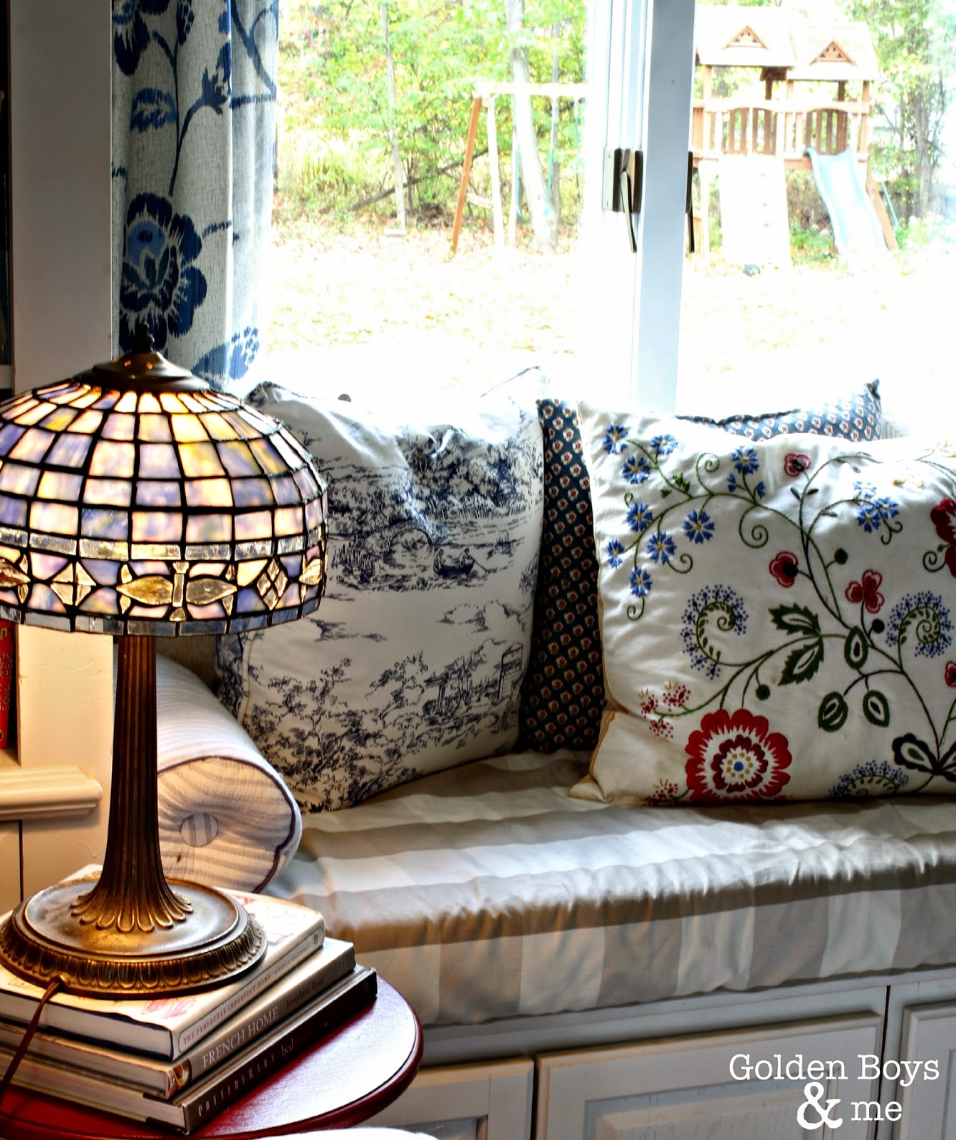Window seat with Ikea pillows and blue stained glass lamp-www.goldenboysandme.com