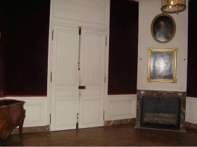 A marble fireplace has been installed also with a reddish tone. Two large  wooden chests are placed on the opposite wall of the fireplace.